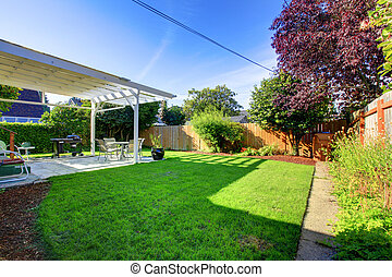 Backyard with fence and house covered deck.