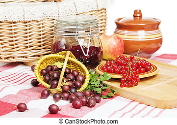 Jam with berries of red currant and gooseberry on the table
