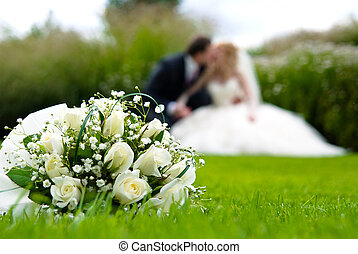 Bridal bouquet of white roses on a green meadow and blurred...