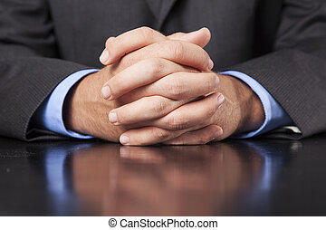 Businessman Hands Clasped - A business man dressed in a suit...