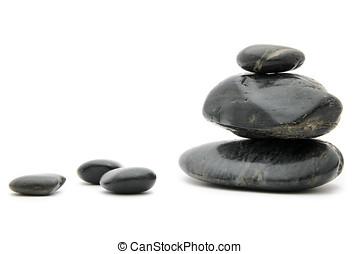 Feng Shui Black Stones - Balanced spa stones on white.