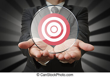 businessman holds target business in round panel glass as...