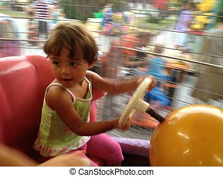 Blurred movements of a Baby enjoying the merry go round -...