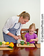 Mother and daughter preparing food Cutting broccoli with...