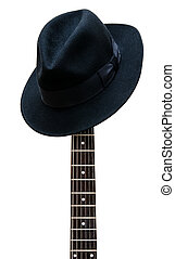 Vintage hat resting on a guitar fretboard isolated...
