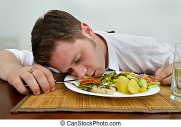 Drunk man sleeping in his dinner plate