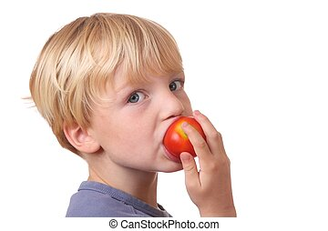 Healthy Eating - Portrait of a young boy eating a tomato