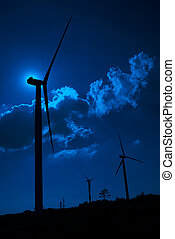 Wind turbine in the back light of the moon with blue sky and...