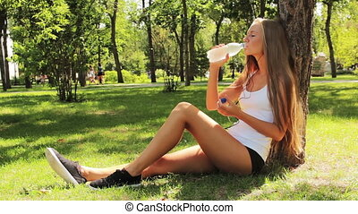 girl - sport girl sitting on the grass, drinking water