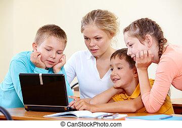 Schoolwork - Smart schoolchildren and teacher working with...