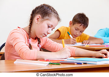 Girl drawing - Portrait of lovely girl drawing in copybook...