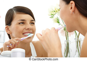 Polishing teeth - Image of pretty female brushing her teeth...