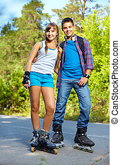 Teenage roller skaters - Couple of happy teens on roller...