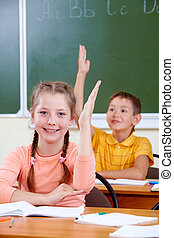 Working at lesson - Portrait of lovely girl raising hand at...