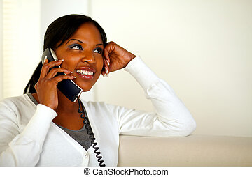 Smiling young woman talking on phone at home - Portrait of a...