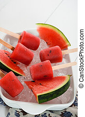 watermelon popsicle in a white bowl with ice and fresch...