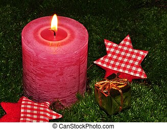 Christmas candle - Burning Christmas candle on moss with a...