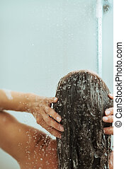 Woman washing hair in shower under water jet. Rear view