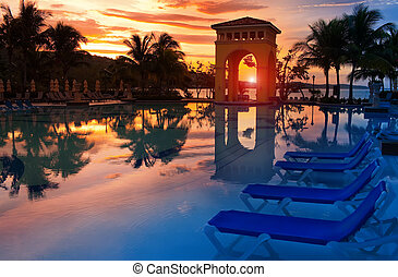 Pavilion on a sunset and the pool with reflection.