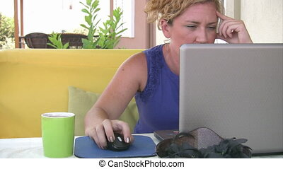 Woman using laptop and smiling to the camera