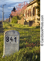 Milestone with old house