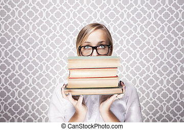 Woman Peering Over Books - A young woman wearing glasses...