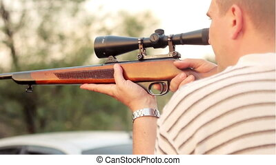 A man fires a rifle with a telescopic sight