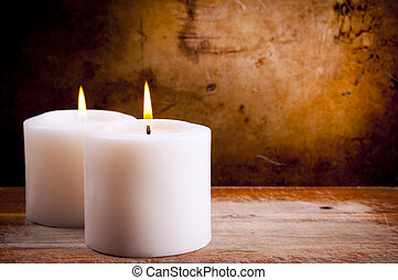 White Candles - White candles burning with a textured...