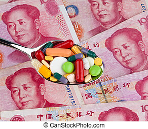 chinese yuan banknotes and pills on a spoon. costs for...