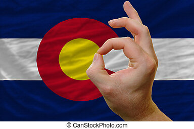 ok gesture in front of colorado us state flag