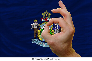 ok gesture in front of maine us state flag