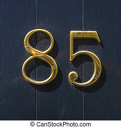 Number 85 - house number eighty-five in gold lettering on a...
