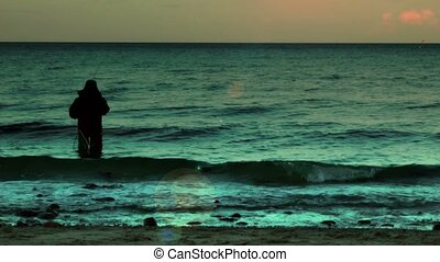 Fisherman in water at sunset