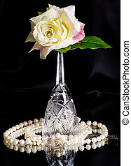 wineglass with white rose on black