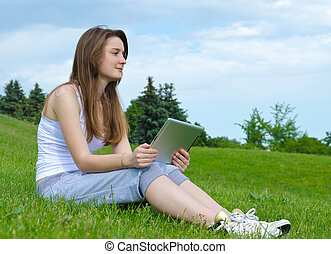 Woman thinking with a tablet in her hands
