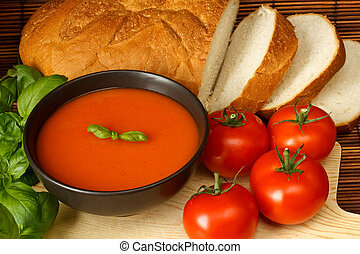 Tomato soup - Bowl of tomato soup with basil garnish, in...
