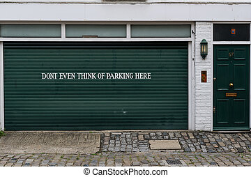 Garage sign prohibiting parking painted on the door of a...