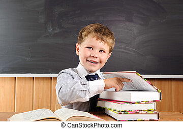 Cheating at exam - Cute elementary aged boy sitting at the...