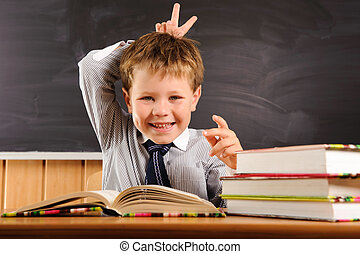 Cute boy fooling at the lesson