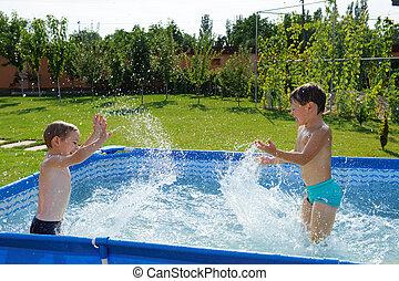Two boys splashing - Two excited boys splashing in swimming...
