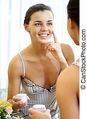 Beauty care - Image of pretty female looking in mirror with...