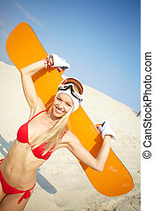 Bikini boarding - Young woman sitting on sand with a...