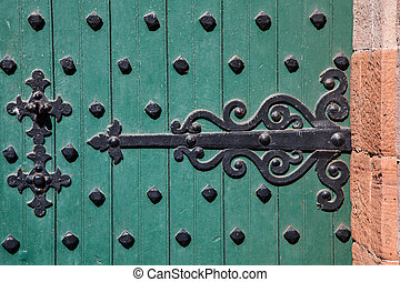 Castle Door Hinge - Ornate wrought iron hinge on a heavily...