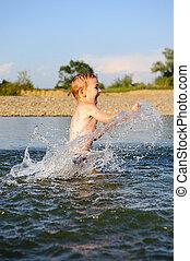 Little boy splashing water in river
