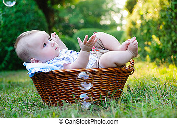 Baby in basket - Cute little boy lying in basket in the park
