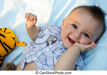 Cute baby boy portrait - Cute little boy lying outdoors in...