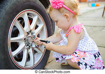 Little child playing in auto mechanic - Cute girl with head...