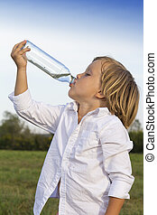 Young boy drinking water outdoors