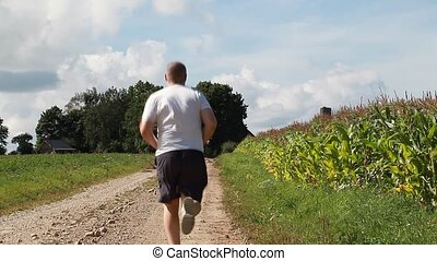 Man running along the corn field in summer