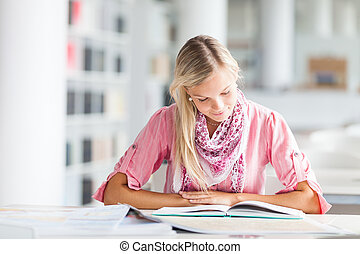 in the library - pretty female student with books working in...